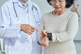 Close-up shot of middle-aged cardiologist standing next to his senior patient and showing her how to use fitness tracker