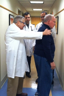"Dr. Stanley Fahn, left, demonstrates the ""pull test"" on a patient for two fellows."